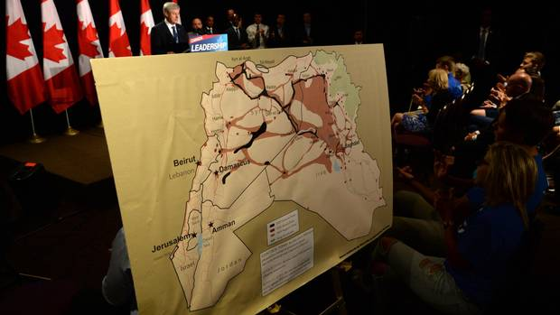 A map showing ISIL zones is displayed as Conservative Leader Stephen Harper delivers a speech during a campaign stop in Ottawa on Sunday, August 9, 2015. Harper announced that if re-elected his party would impose banned travel zones to combat terrorism. (Sean Kilpatrick/The Canadian Press)